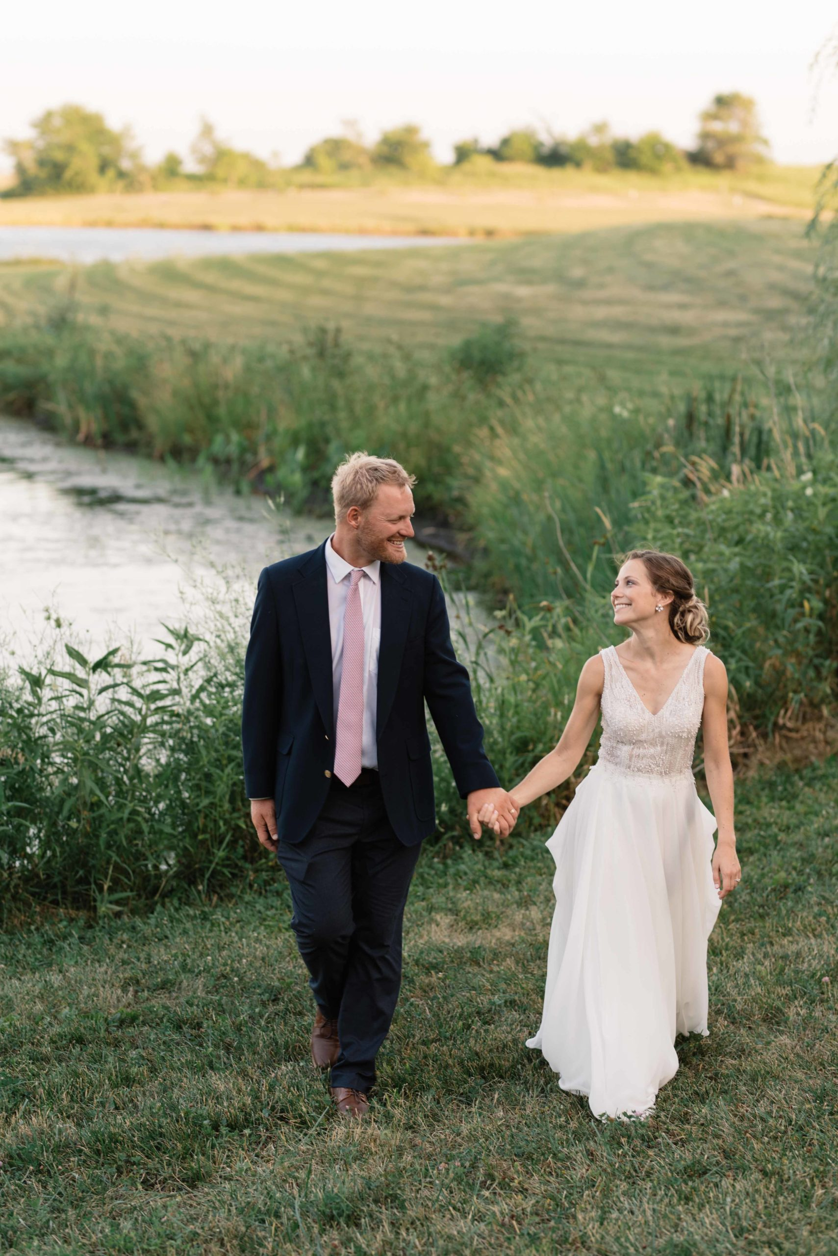bride and groom holding hands walking near pond at sunset at schafer century barn wedding venue near des moines iowa