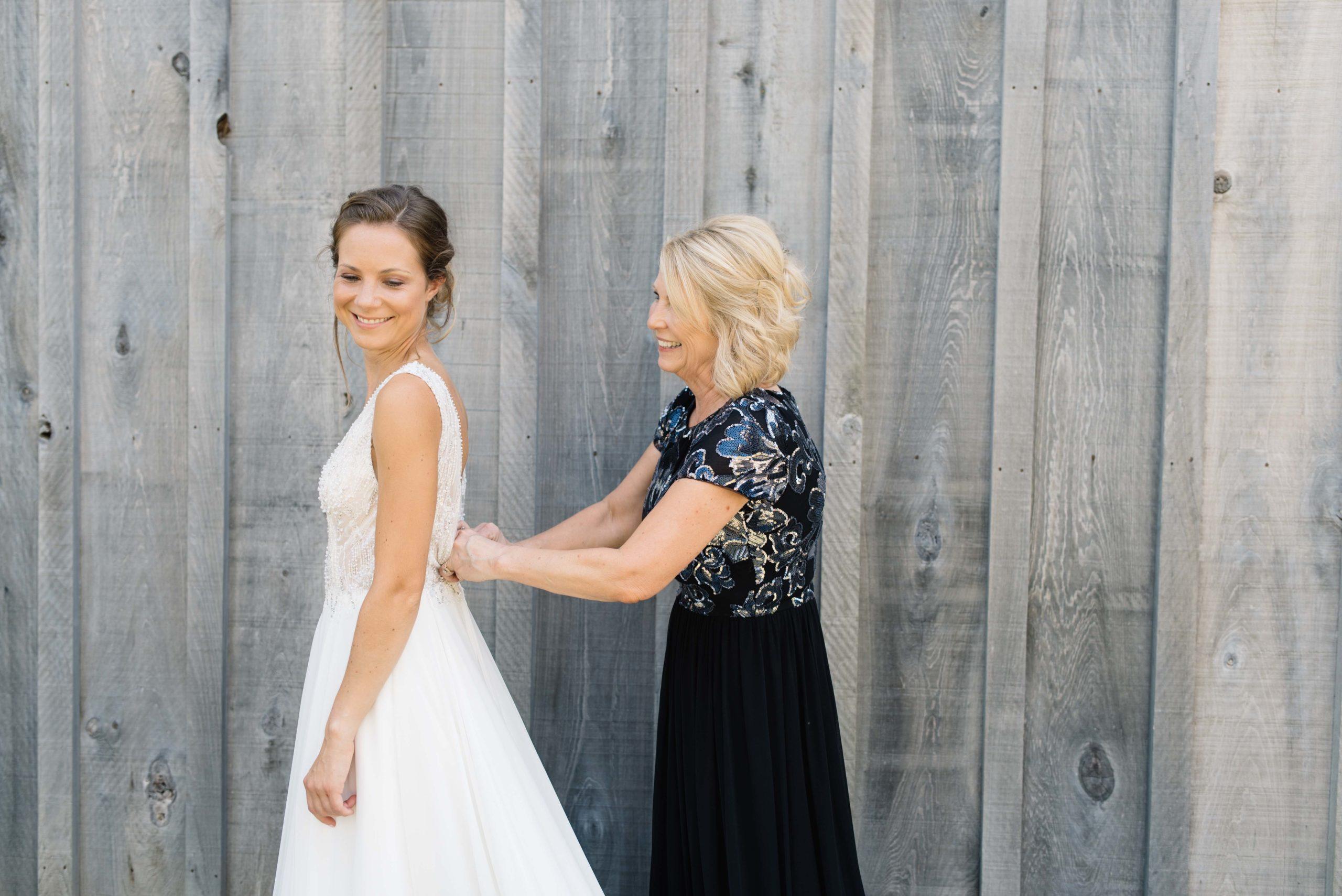 mom helping bride button wedding dress schafer century barn wedding venue