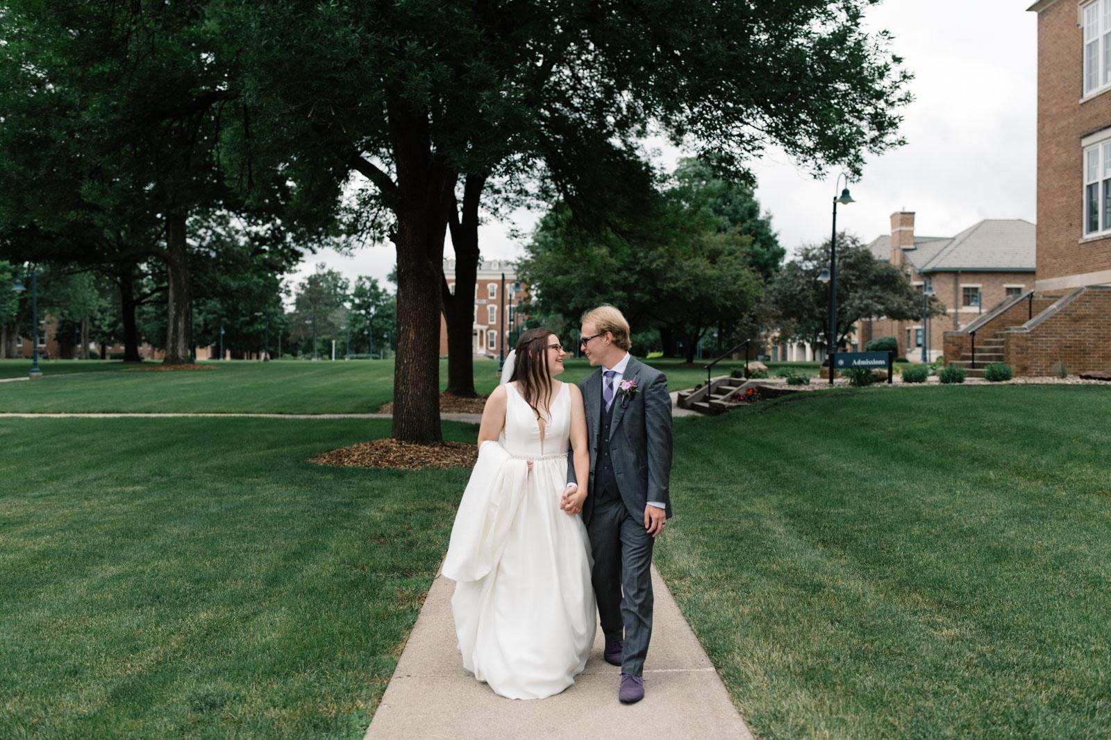 bride and groom walking outside wartburg college wedding