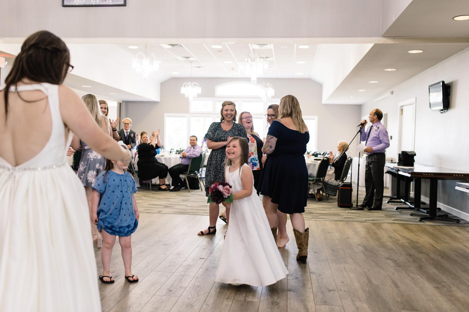 flower girl catches bouquet at fox ridge golf course wedding reception
