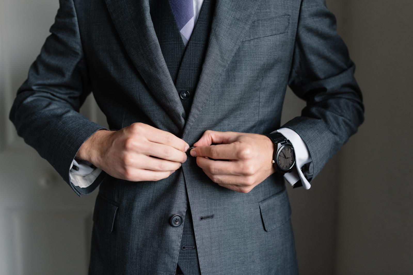 groom buttoning suit jacket iowa wedding