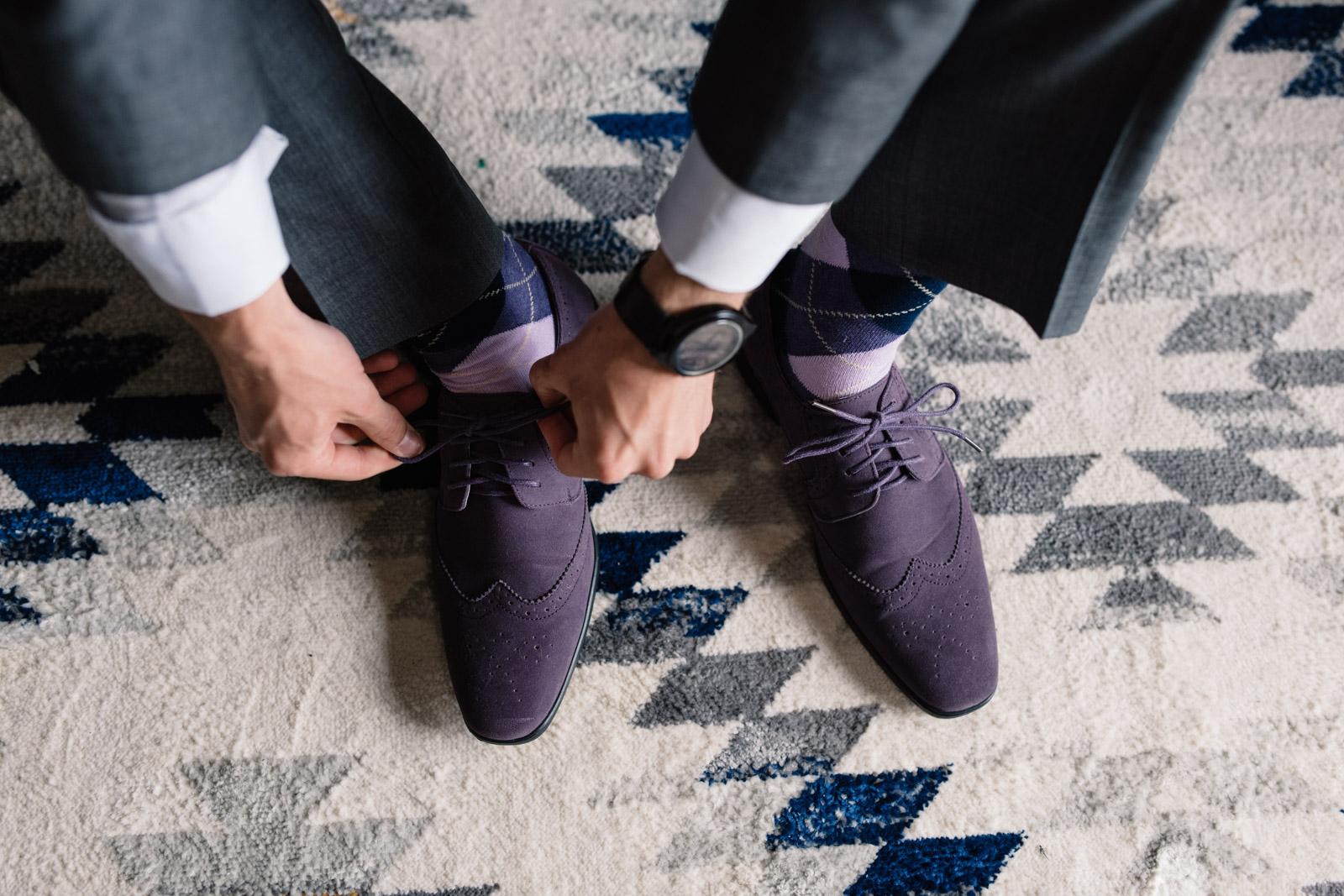 groom tying purple suede dress shoes iowa wedding