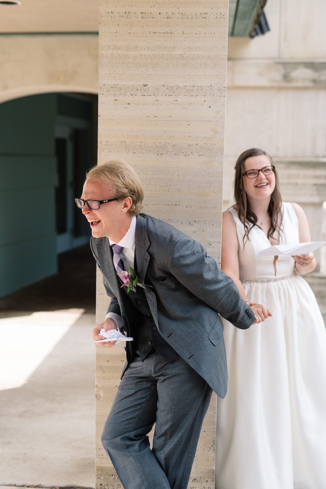 groom laughing while reading letters wartburg college wedding
