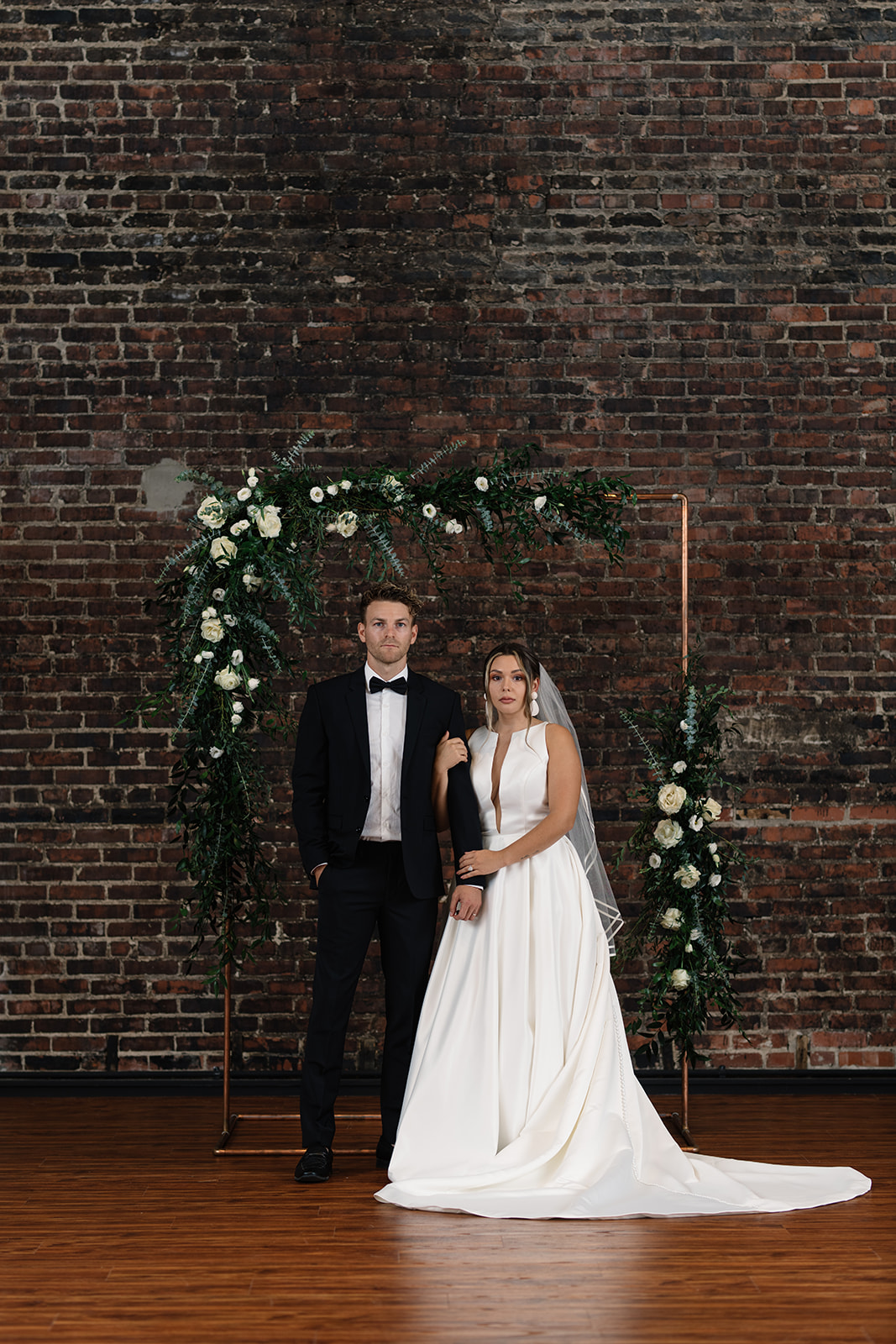 white rose floral copper arbor on brick wall olympic south side wedding venue