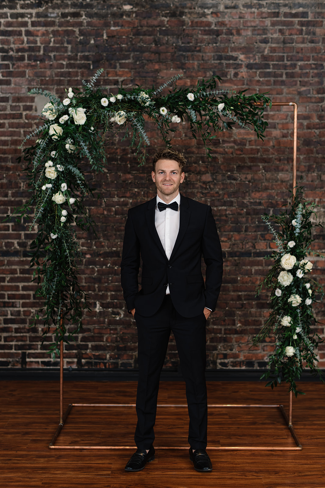 groom in tux under white rose copper arbor olympic south side theater weding venue anne and ellis events