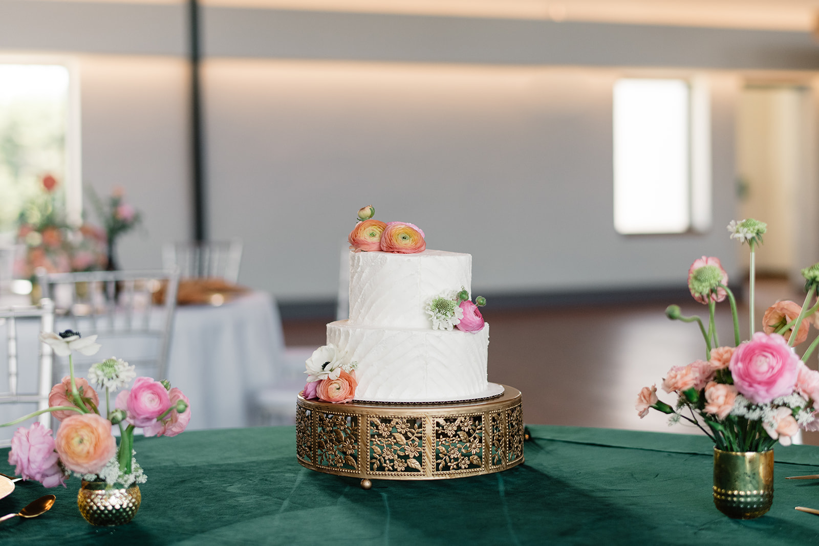 white wedding cake on gold stand with pastel florals
