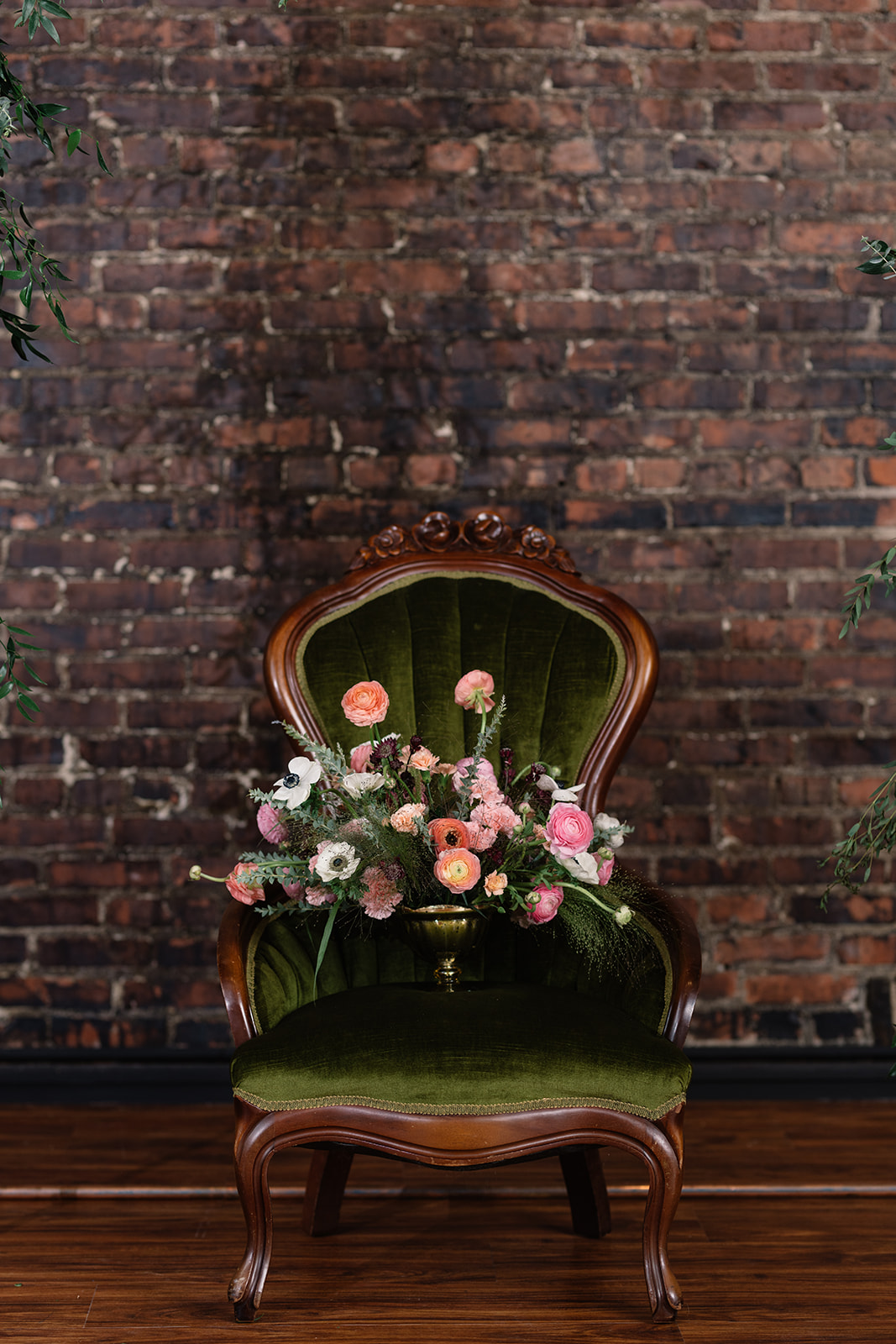 bold wedding bouquet green velvet chair brick wall