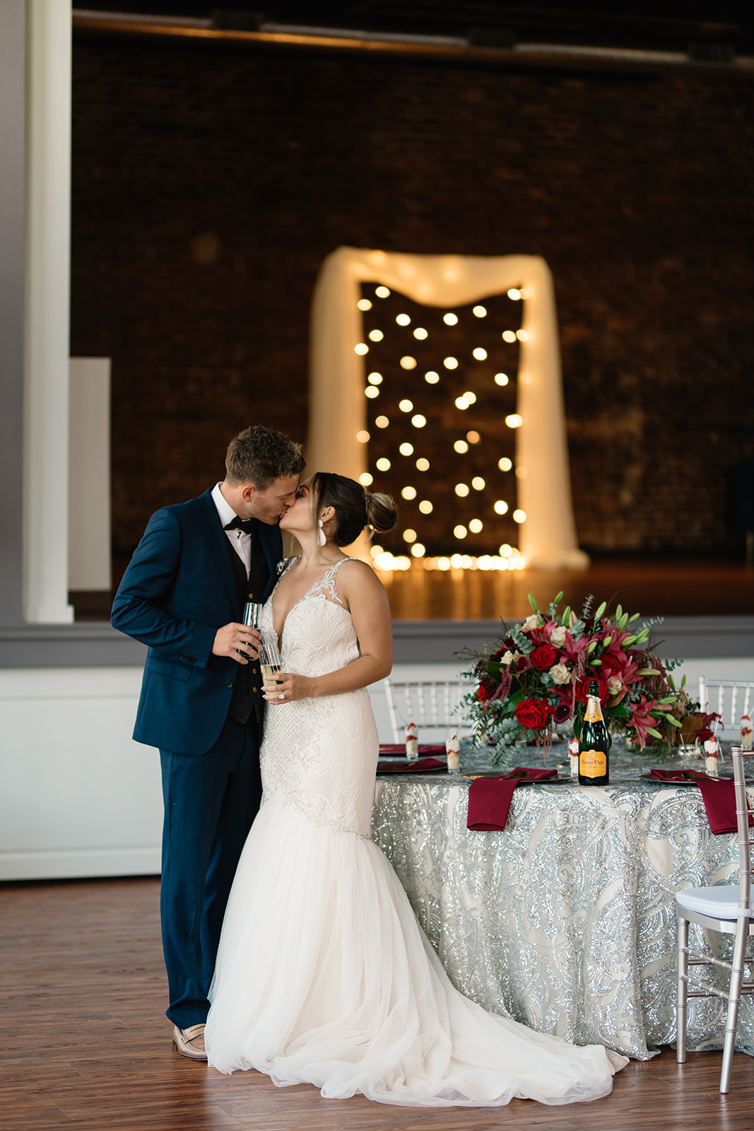 couple under twinkly light wedding arch brick wall olympic south side theater wedding venue cedar rapids