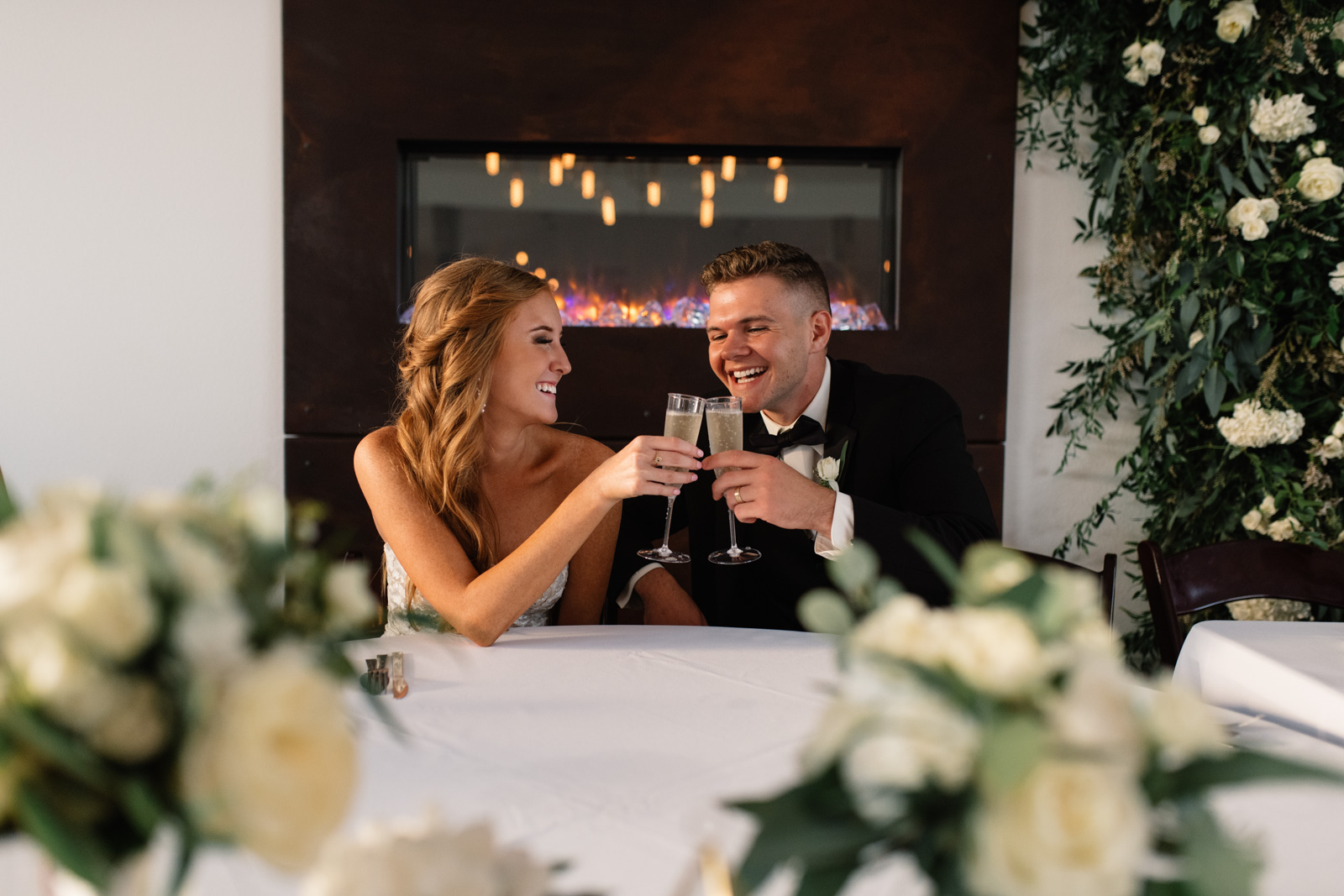 bride and groom toast champagne by fireplace koru berry farm wedding venue