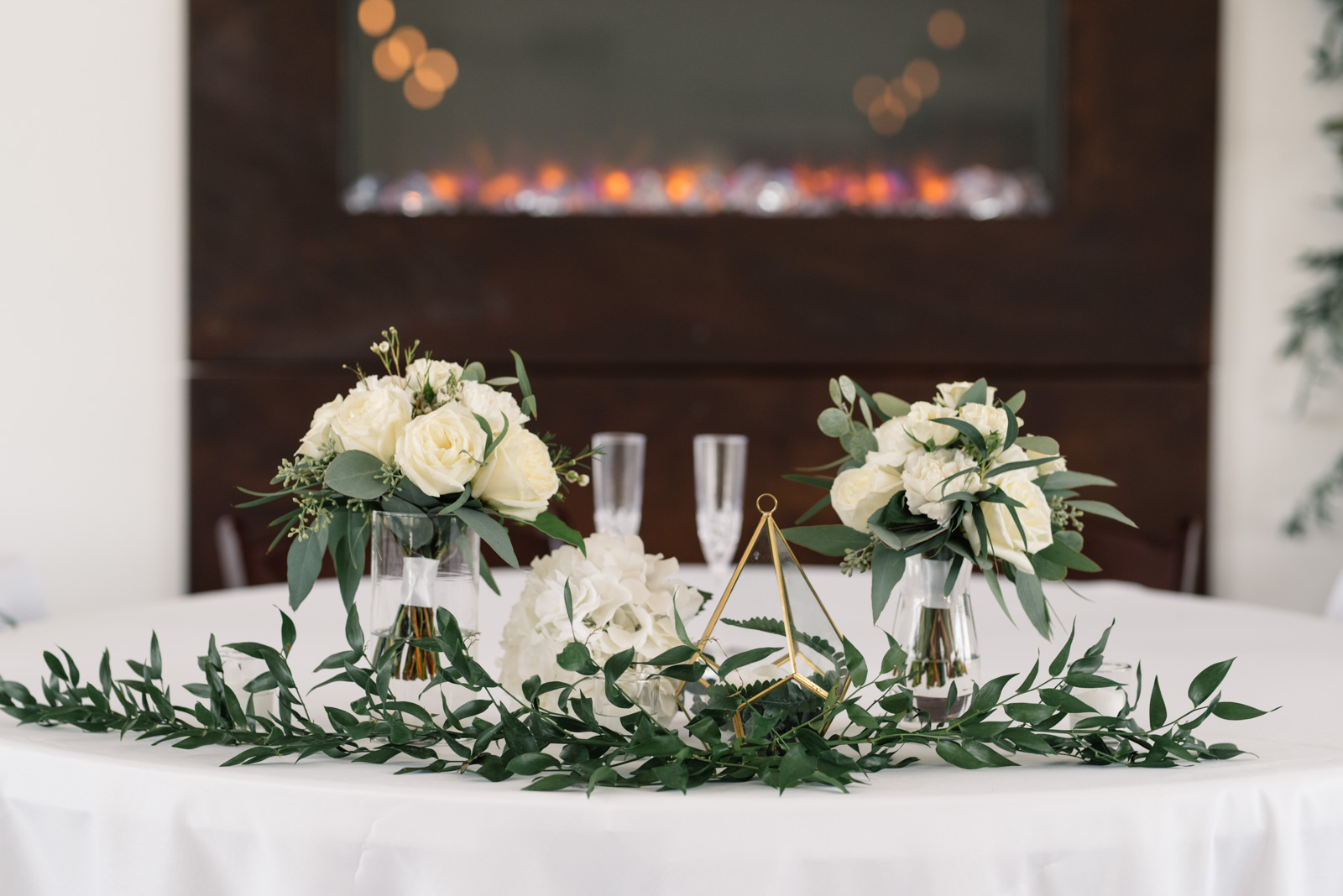 head table decor gold and greenery fireplace koru berry wedding venue