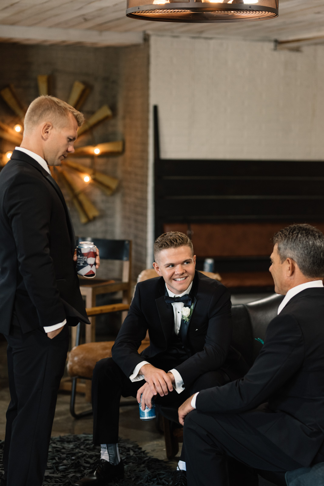 groom and best man helping father of the groom tie tie