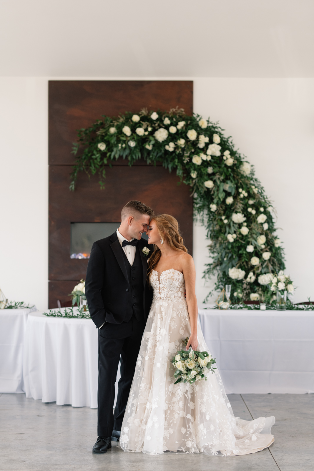 bride and groom pose under floral arch and fireplace koru berry farm wedding venue