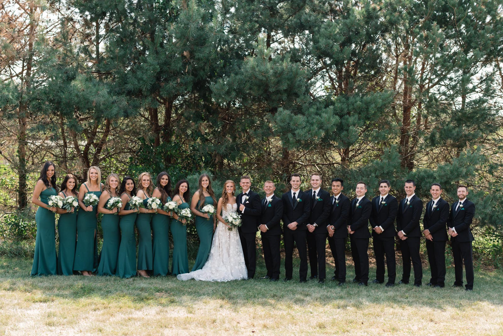 bridal party green bridesmaids dresses and black tuxes koru berry farm wedding venue