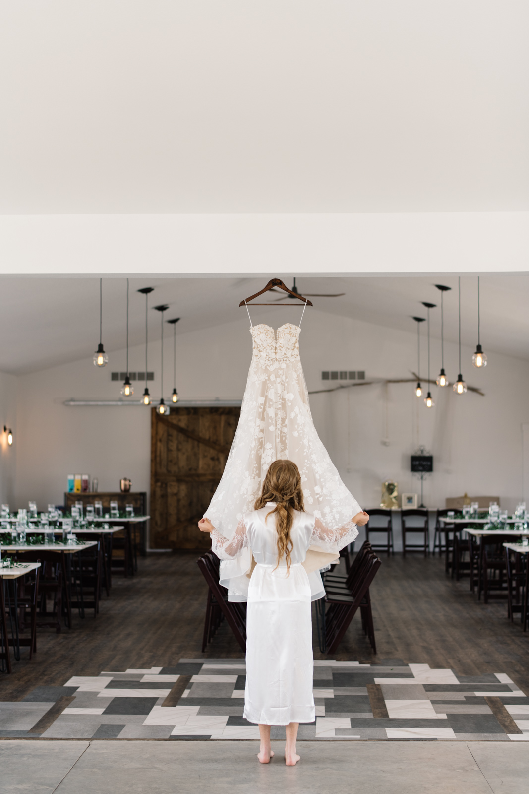 bride fluffs wedding dress hanging at iowa wedding venue