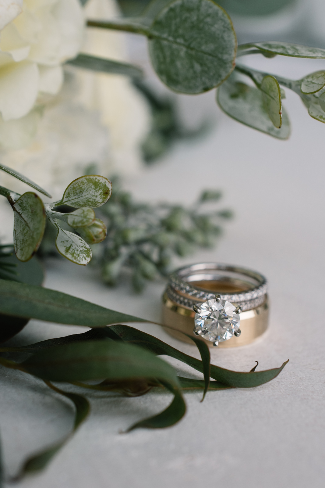 wedding rings in white rose and greenery floral bouquet