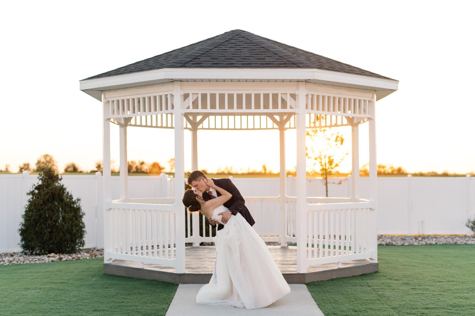 groom dips bride in gazebo at sunset epic event center cedar rapids wedding venue