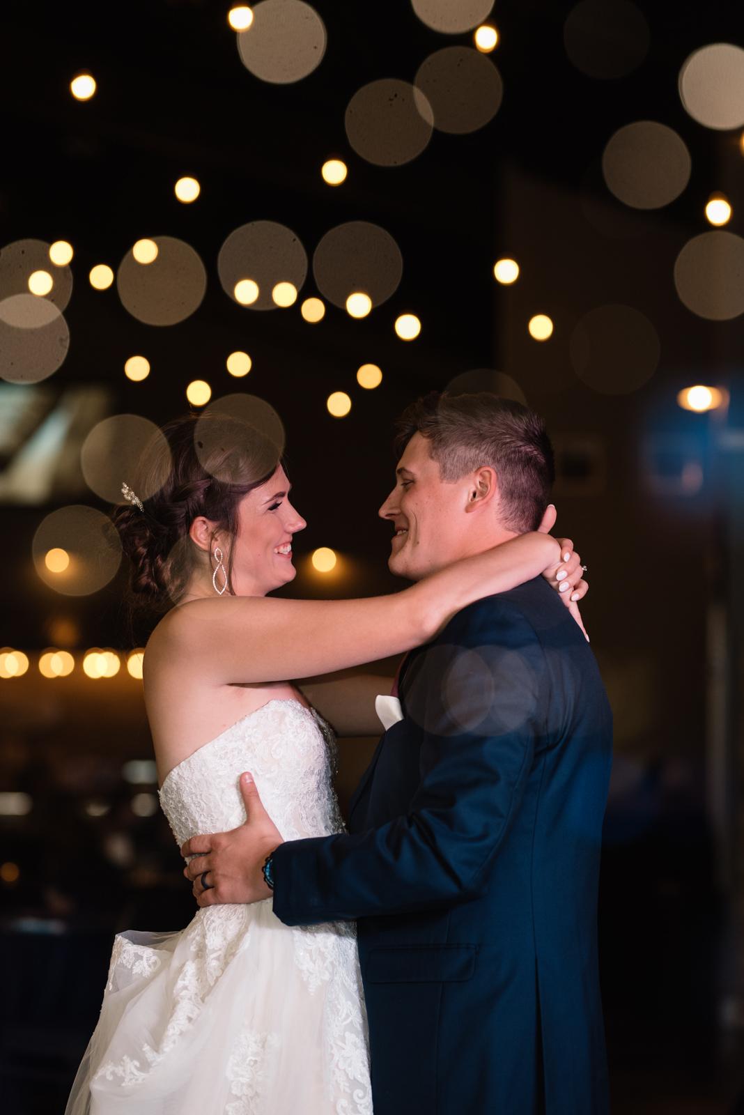 bride and groom first dance under edison bulb lights epic event center cedar rapids wedding venue