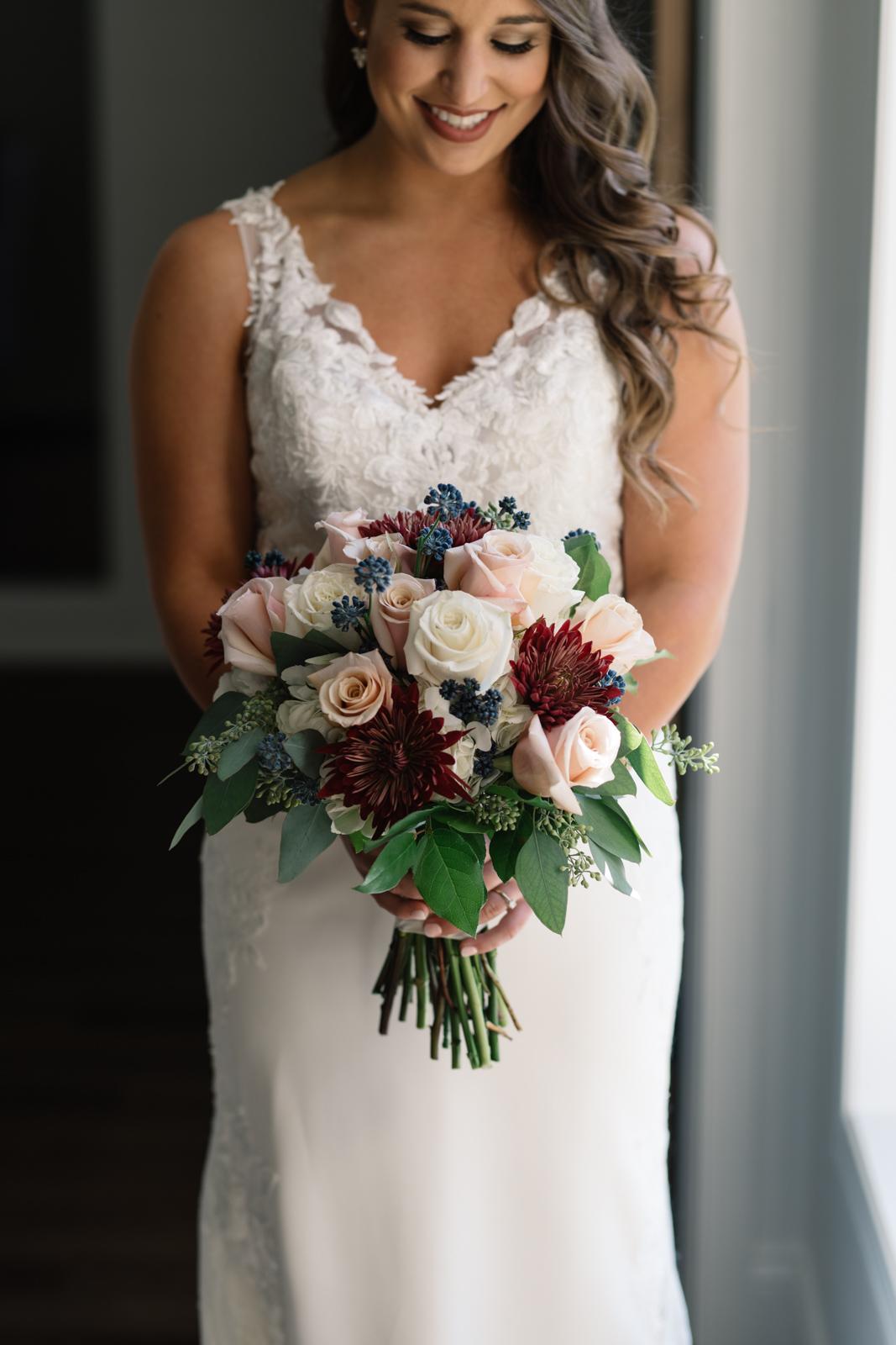 bride holding bouquet in window light bella sala bridal suite