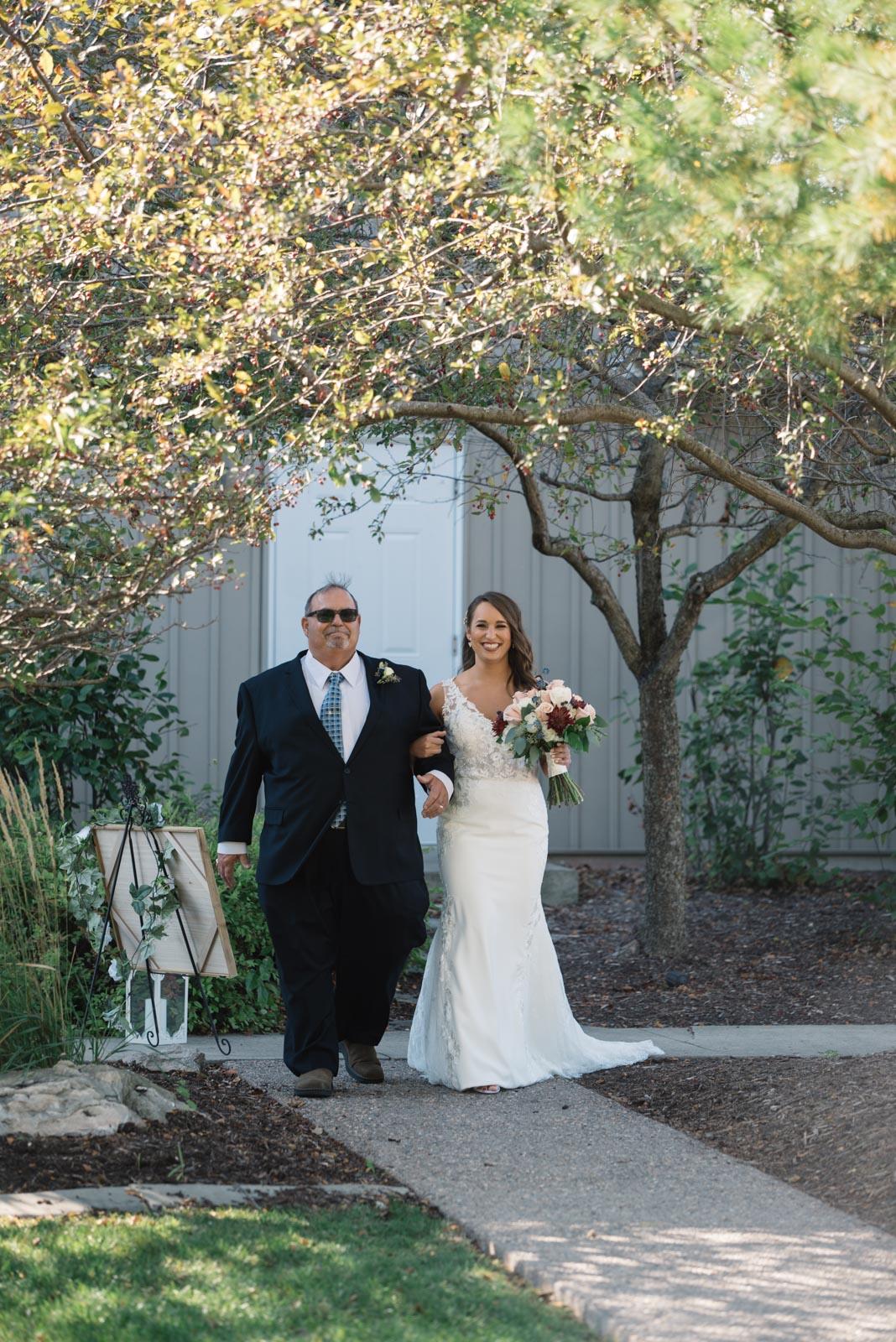 dad walking bride down the aisle outdoor wedding ceremony bella sala wedding venue in tiffin iowa