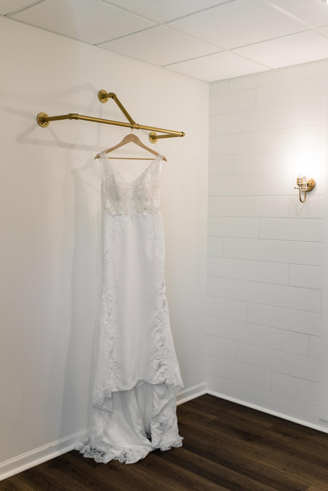 wedding dress hanging on gold bar bella sala wedding venue cedar rapids wedding photographer
