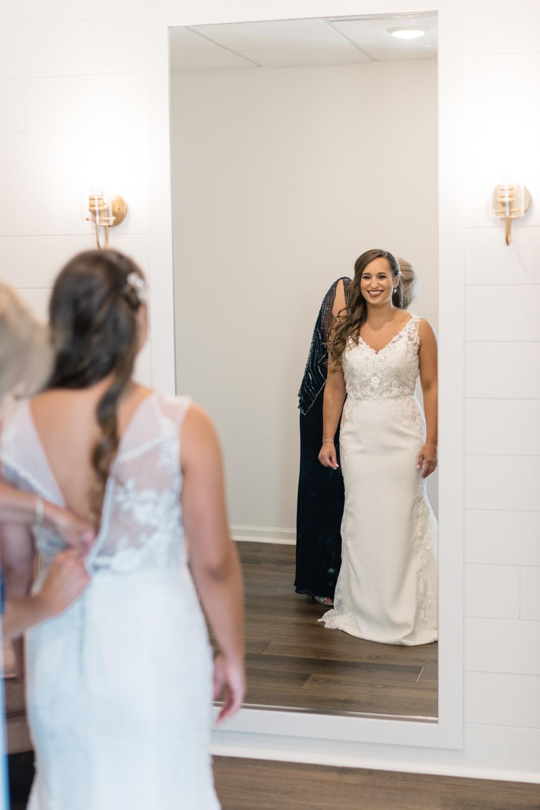 mom helping bride put on wedding dress bella sala in bridal suite bella sala wedding venue