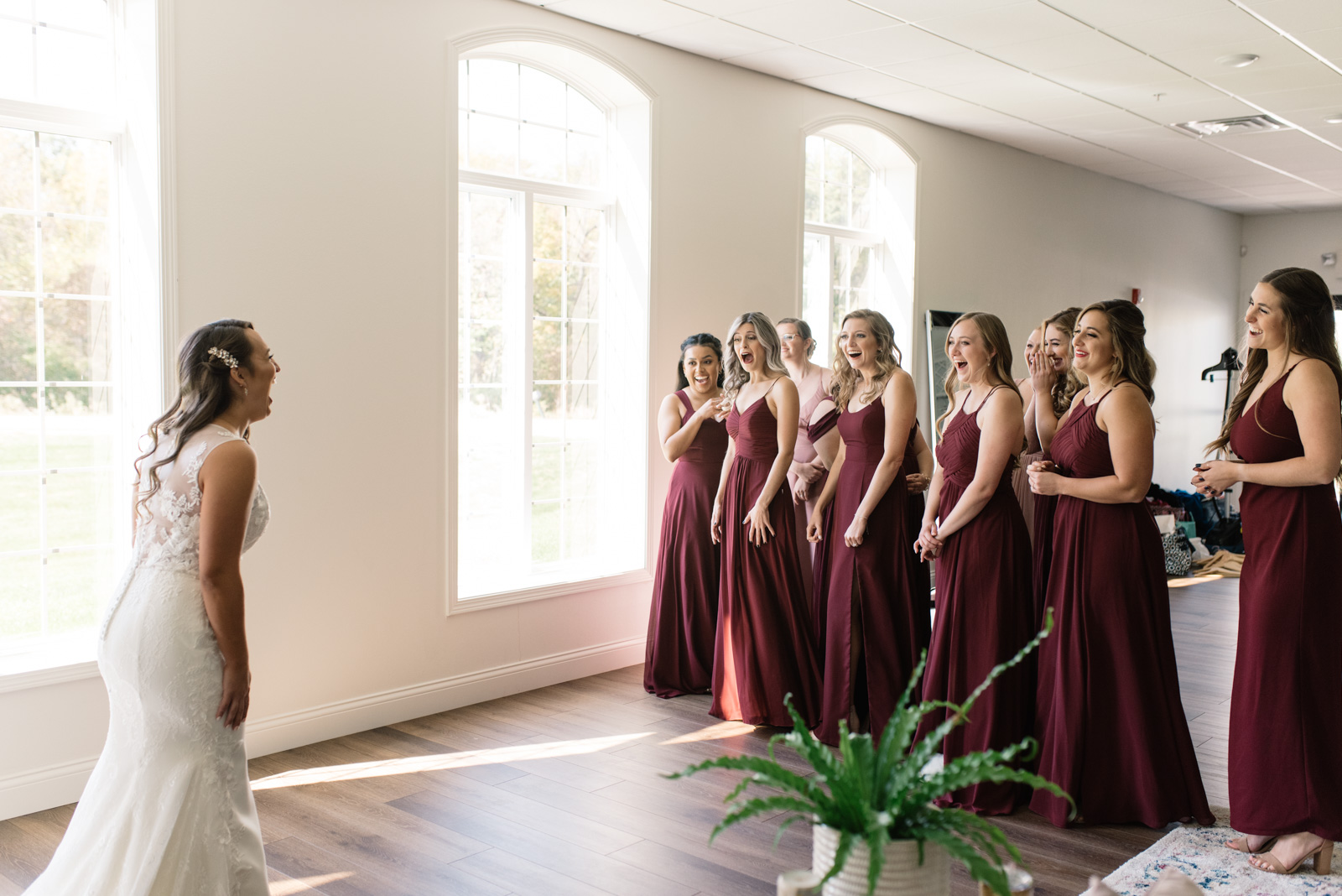 bride revealing wedding dress to bridesmaids during first look bella sala bridal suite